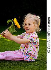 Child with a sun flower in the garden in summer