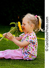 child with a sunflower in the garden in summer