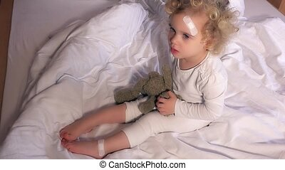 Child with adhesive bandage applied to head and leg. Toddler...