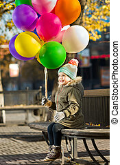 child with air-balloons - happy little child sit on bench ...