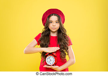 child with alarm clock. Timeless fashion. beauty hairdresser. parisian child on yellow background. cute girl with long curly hair in beret. little girl in french style hat. modern and retro fashion