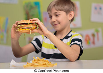 Child with appetite for hamburger