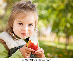 Child with apple in autumn park