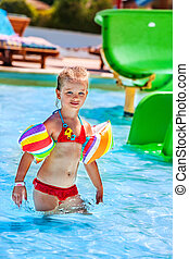 Child with armbands playing in swimming pool. - Child in reb...