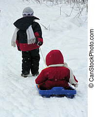 child with baby on sled