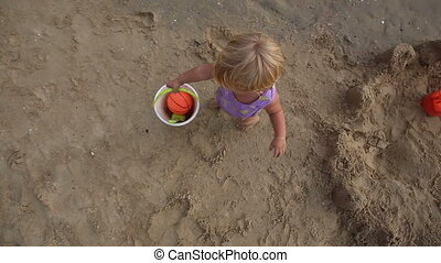 child with ball in the bucket goes to the sea