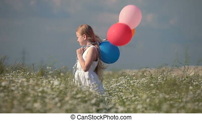 Child with balloons on spring blooming meadow