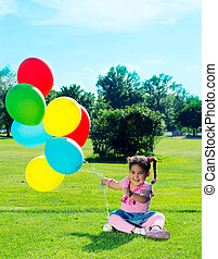 Child with balloons on the field