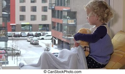 Child with best friend teddy bear caress and kiss looking at...