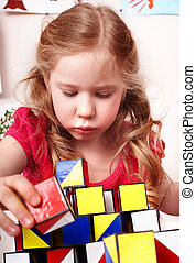 Child with block  in play room.
