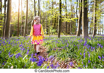 Child with bluebell flowers in spring forest - Child with...