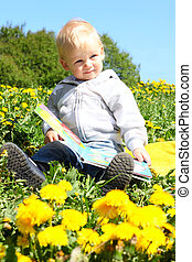 Child with boor outdoor - Small child sitting with book on...
