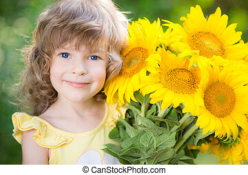 Child with bouquet of beautiful sunflowers