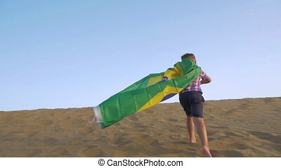 Child with Brazilian flag running on the sand