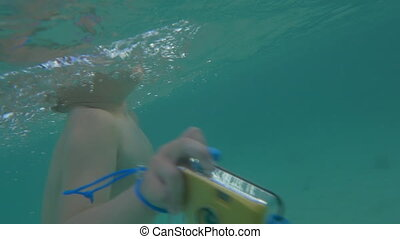 Child with camera in waterproof case bathing in the sea