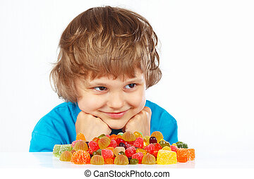 Child with candies on white background