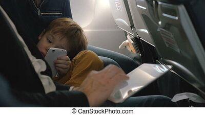 Child with cell and and man using pad in plane