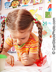 Child with chalk draw in playroom.
