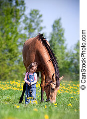 Child with chestnut horse in field
