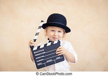 Child with clapper board playing at home.