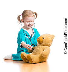child girl with clothes of doctor playing with plush toy