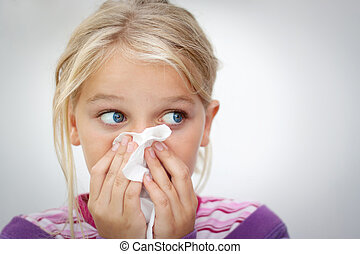 Child with cold - Girl blowing her nose. Space for text....