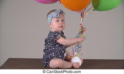 Child with colorful balloons. Little girl winks and smiles.