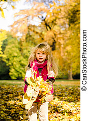 child with colorful leaves