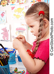 Child with colour pencil in play room.