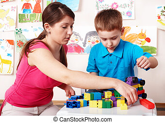 Child with construction  in play room.