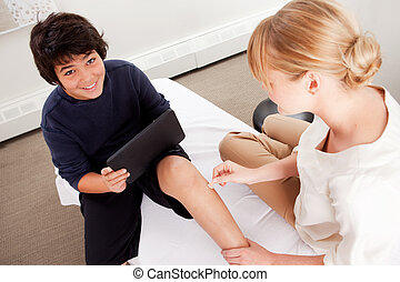 Child with Digital Tablet During Acupuncture - Young male...