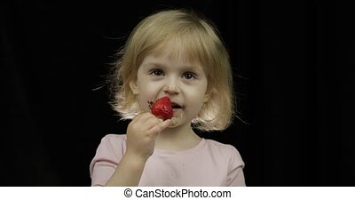 Child with dirty face from melted chocolate and whipped cream eats strawberry