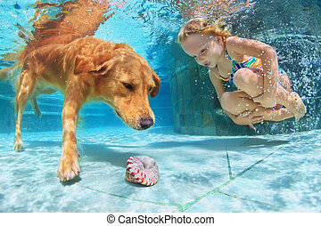 Child with dog dive underwater - Little child play with fun...