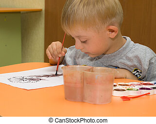 Child with Down syndrome is drawing on a sheet of paper...