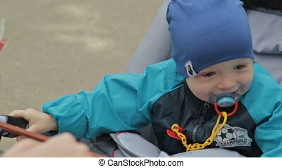 Child with dummy is sitting in a carriage, Slowmotion -...