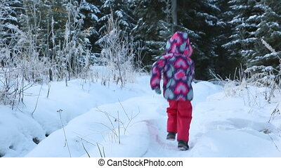 Child with fir branch running through the snow forest