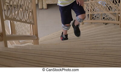 Child with foot drop system walking upstairs. FES therapy