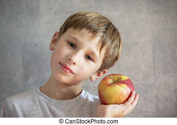Child with fruit. Funny boy with huge apples