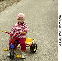 Child with funny expression sitting on a tricycle