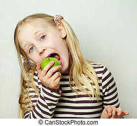 Child with green apple - healthy concept, humor