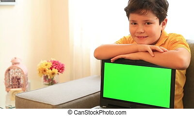 Child with green screen laptop monitor