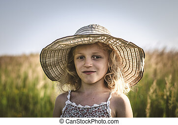child with hat in the field