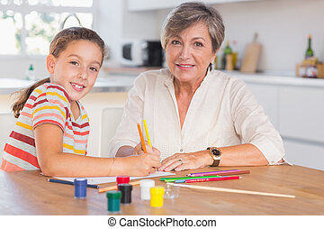 Child with her grandmother looking at the camera while drawing