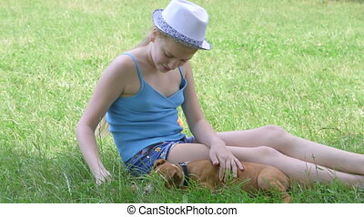 Child with her puppy dog sitting, on a green lawn