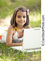 Child with laptop at park.