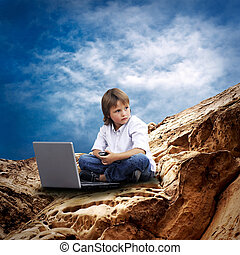 Child with laptop on the mountain under sky with clouds