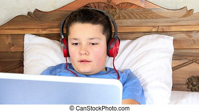 Child with laptop - School boy with headphone using laptop...