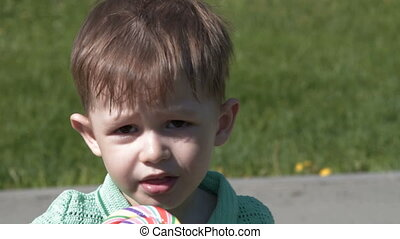 Child with lollipop in the park