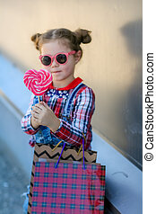 Child with Lollipop on a stick in his hands on the background of the wall