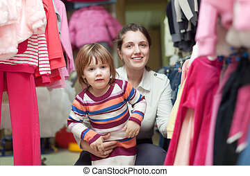 child with mother at clothes shop